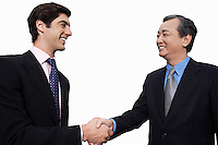 Happy businessmen shaking hands over white background