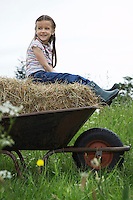 Girl (5-6) sitting on hay in wheelbarrow in field portrait