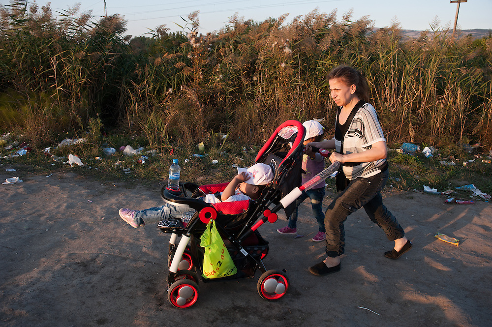 Sunday 13th of September 2015, afternoon. Aysha is carrying Bisan through a field meters away from the Macedonian - Serbian border. About an hour ago a train full of immigrants and refugees arrived at the border village of Slanishte after 4 hrs of travelling across the Republic of Macedonia. A group of Danish volunteers gave Aysha a pram to carry her daughters. The path is uneven and it will take her more than an hour to walk to the Serbian town of Preshevo.