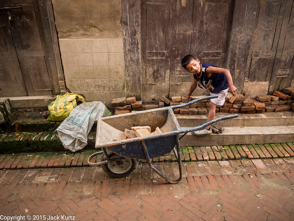 02 AUGUST 2015 - BHAKTAPUR, NEPAL:  A boy in Bhaktapur picks up bricks that will be used in an Internal Displaced Person (IDP) camp for people in Bkaktapur left homeless by the earthquake. The Nepal Earthquake on April 25, 2015, (also known as the Gorkha earthquake) killed more than 9,000 people and injured more than 23,000. It had a magnitude of 7.8. The epicenter was east of the district of Lamjung, and its hypocenter was at a depth of approximately 15km (9.3mi). It was the worst natural disaster to strike Nepal since the 1934 Nepal–Bihar earthquake. The earthquake triggered an avalanche on Mount Everest, killing at least 19. The earthquake also set off an avalanche in the Langtang valley, where 250 people were reported missing. Hundreds of thousands of people were made homeless with entire villages flattened across many districts of the country. Centuries-old buildings were destroyed at UNESCO World Heritage sites in the Kathmandu Valley, including some at the Kathmandu Durbar Square, the Patan Durbar Squar, the Bhaktapur Durbar Square, the Changu Narayan Temple and the Swayambhunath Stupa. Geophysicists and other experts had warned for decades that Nepal was vulnerable to a deadly earthquake, particularly because of its geology, urbanization, and architecture.      PHOTO BY JACK KURTZ