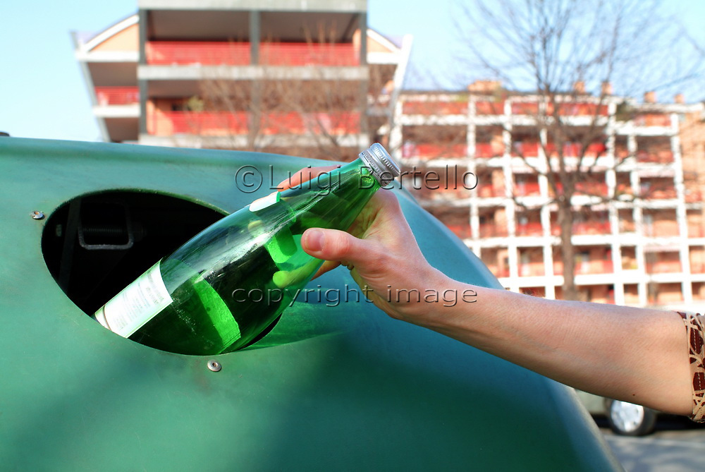 Detail of a female hand disposing of a glass bottle in a proper container with a palace in the background