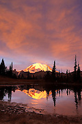 Mount Rainier, under a fiery sunrise, is reflected in Tipsoo Lake, located near Chinook Pass, Washington.