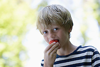 Portrait of boy (5-6) eating strawberry