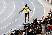 epa02898248 Usain Bolt from Jamaica cruises past photographers as he winds down after crossing the finish line in the mens 4x100m relay final during the 13th IAAF World Championships in Daegu, Republic of Korea, 04 September 2011. The Jamaicans set a new world record of 37.04  EPA/NIC BOTHMA