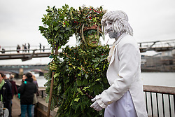 © Licensed to London News Pictures. 05/01/2020. London, UK. The Holly Man greets a street performer on Bankside as a group of actors mark Twelfth Night, an annual celebration the New Year. Photo credit: Rob Pinney/LNP