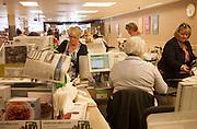 People at supermarket check-outs inside Waitrose store, Marlborough, Wiltshire, England, UK