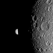 Saturn's moon Mimas peeks out from behind the night side of the larger moon Dione in this Cassini image.