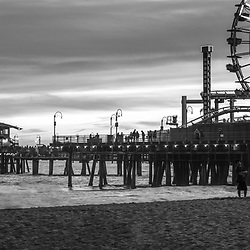 Santa Monica Pier black and white panorama photo at sunset at Santa Monica Beach. Santa Monica Pier is along the Pacific Ocean in Southern California in he United States. Panoramic photo is 1:3. Copyright ⓒ 2017 Paul Velgos with All Rights Reserved.