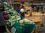29 FEBRUARY 2016 - BANGKOK, THAILAND:  Workers unload lettuce in the produce section of the Bangkok flower market. Many of the sidewalk vendors around Pak Khlong Talat, the Bangkok flower market, closed their stalls Monday. As a part of the military government sponsored initiative to clean up Bangkok, city officials announced new rules for the sidewalk vendors that shortened their hours and changed the regulations they worked under. Some vendors said the new rules were confusing and too limiting and most vendors chose to close Monday rather than risk fines and penalties. Many hope to reopen when the situation is clarified.   PHOTO BY JACK KURTZ