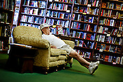 "SHOT 8/12/09 2:05:53 PM - Catching a quick nap on a couch at the the Tattered Cover Book Store on Colfax Avenue in Denver, Co. Colfax Avenue is the main street that runs east and west through the Denver-Aurora metropolitan area in Colorado. As U.S. Highway 40, it was one of two principal highways serving Denver before the Interstate Highway System was constructed. In the local street system, it lies 15 blocks north of the zero point (Ellsworth Avenue, one block south of 1st Avenue). For that reason it would normally be known as ""15th Avenue"" but the street was named for the 19th-century politician Schuyler Colfax. On the east it passes through the city of Aurora, then Denver, and on the west, through Lakewood and the southern part of Golden. Colloquially, the arterial is referred to simply as ""Colfax"", a name that has become associated with prostitution, crime, and a dense concentration of liquor stores and inexpensive bars. Playboy magazine once called Colfax ""the longest, wickedest street in America."" However, such activities are actually isolated to short stretches of the 26-mile (42 km) length of the street. Periodically, Colfax undergoes redevelopment by the municipalities along its course that bring in new housing, trendy businesses and restaurants. Some say that these new developments detract from the character of Colfax, while others worry that they cause gentrification and bring increased traffic to the area. (Photo by Marc Piscotty / © 2009)"