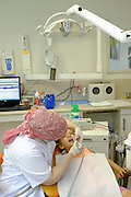 Young girl has her teeth cleaned by a dental hygienist at the dentist