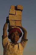 Child carrying bricks. In areas of Madagascar where the soil is lateritic houses are built from home-made bricks. It is a labour intensive process from digging up surrounding soil, individually moulding them, building kilns and using large quantities of fire wood. Dried bricks are then carried on the heads of usually the women and children to where they are to be used or sold.<br />