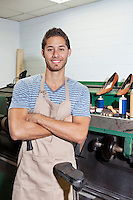Portrait of young shoemaker standing with arms crossed in workshop