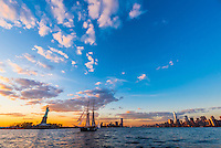 A sailing ship in New York harbor with Statue of Liberty on left and skyline of Lower Manhattan on right, New York, New York USA.