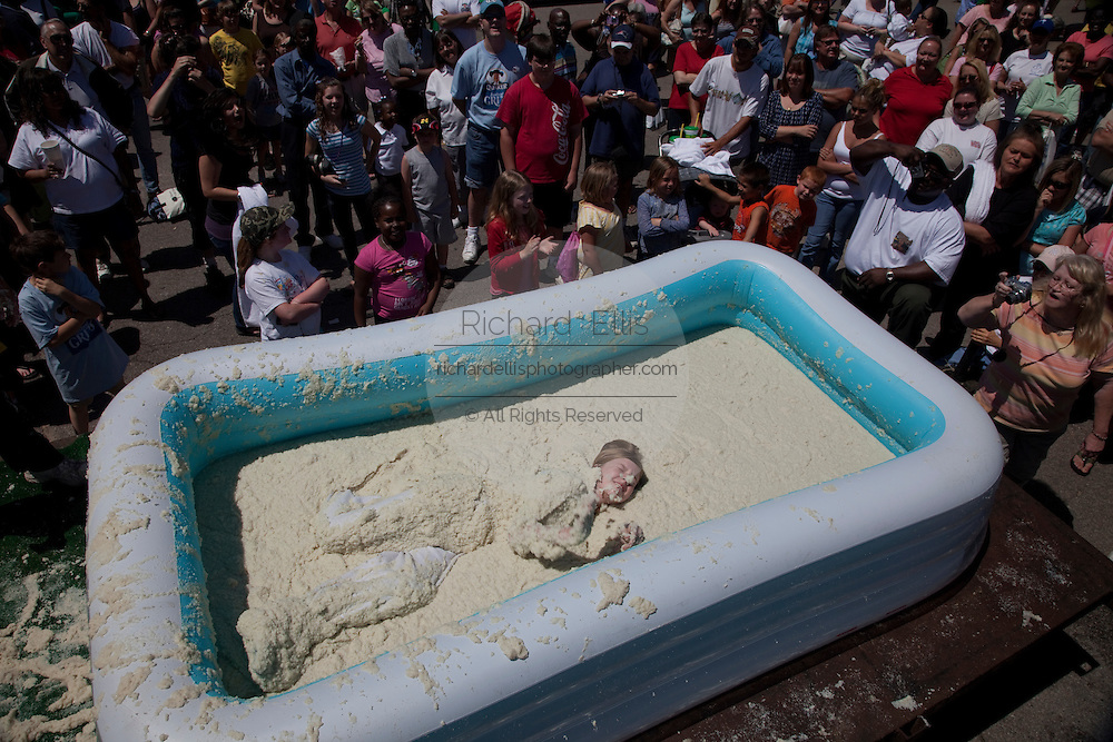 ST GEORGE, SC - APRIL 18: A young girl rolls around in a giant vat of grits April 18, 2009 during the World Grits Festival in St. George, SC. The winner is the one who can hold the most of the stick grits to their body.     (Photo Richard Ellis)