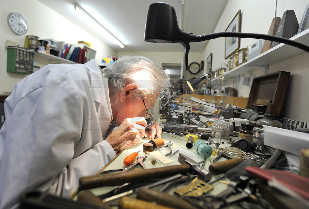 """©London News pictures...28/10/2010.  Dudley Taylor, 76, a clockmaker all his life working at his desk. Staff at Horological Workshops start the task of changing the 100's of clocks at their store in Guildford, Surrey, UK. Micahel Tooke who has owned the store for 43 years and worked in the clock business all his life said. """"at this time of year we get alot of people who bring clocks in for repair after they have changed the time incorreectly by winding back the hands manually"""""""