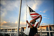 Steven St. John/Tribune..As he does every day, resident Keith Mager brings in the American flag at sunset on Saturday evening, June 30, 2007 New Mexico Veterans Integration Center.