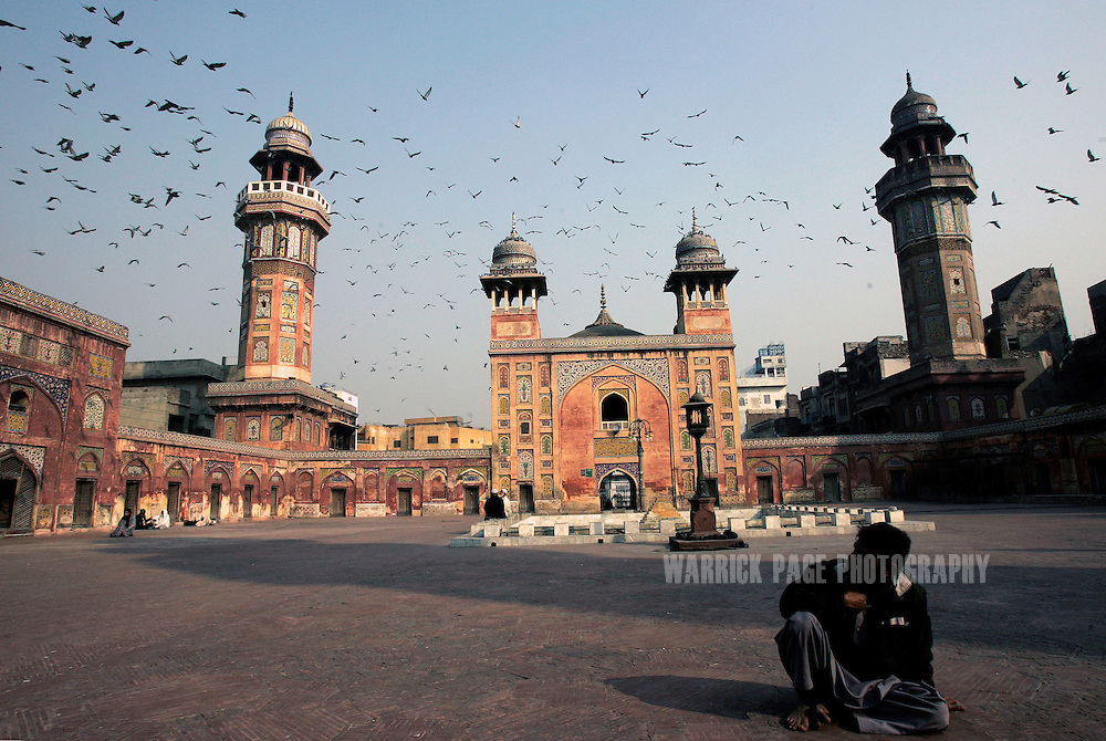 LAHORE, PAKISTAN - JANUARY 29: A muslim man watches a flock of birds fly over the Wazir Khan Mosque in the Old City, Lahore, Pakistan on Monday 29 January, 2007. Shiite Muslims around the world commemorate the martyrdom of the Prophet Mohammed's grandson, Imam Hussein, who was killed during the battle of Karbala, Iraq. Security has been increased throughout Pakistan due to fears of sectarian violence after suicide bombings in Islamabad and Peshawar last week claimed the lives of 15 people. (Photo by Warrick Page)
