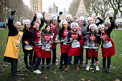 © Licensed to London News Pictures. 13/02/2018. London, UK. The Media team pose for a photo after winning the Rehab Parliamentary Pancake Race 2018 in Victoria Tower Gardens. The Parliament Team - made up of MPs, Lords and Ladies - race in a relay against the Media Team - made up of reporters and presenters - whilst continuously flipping pancakes to celebrate Shrove Tuesday, also known as Pancake Day. Photo credit : Tom Nicholson/LNP