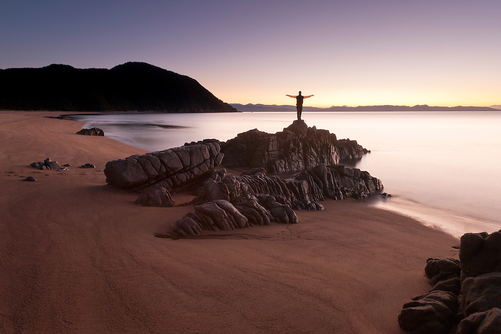 A man stands on rocks at a beach at dusk with arms outstretched, Whariwharangi Bay, Abel Tasman National Park, New Zealand.