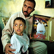 30 May 2004..Baghdad, Iraq...Mehdi martyrs.......Raad Yasim aged 47 sits with his grandson Jaffar aged 4...Jaffar's father Uday Yasim aged 27 was killed on the 13th May during clashes between US Forces and Medhi army in Sadr city...Uday's family have always been supporters of the Sadr family, the Mehdi army are the private militia of Moqtada al-Sadr the firebrand cleric opposing the US occupation...The death of Uday has reinforced the families will to fight against coalition forces.