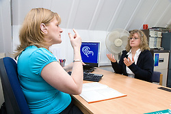 Welfare rights officer and client signing as they fill in Disability Living Allowance form at The Nottinghamshire Deaf Society,