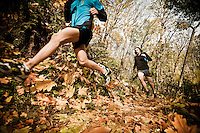 Two men trail running through a forest in the Fall colors.