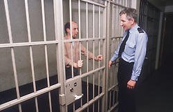 Man standing in police cell talking to police officer through metal bars,
