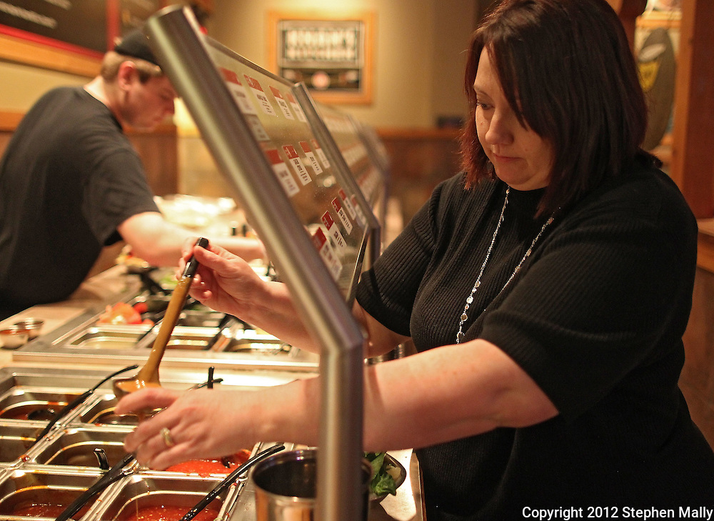 Julie Penrod fills a cup with sauce for her dish at Genghis Grill, 2230 Edgewood Road SW, in Cedar Rapids on Thursday evening, March 1, 2012. Penrod is eating at Genghis Grill every evening for 60 days as a Health Kwest Khantestant. (Stephen Mally/Freelance)