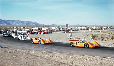 "Denny Hulme (5) and Bruce Mclaren (4), aka ""The Bruce and Denny Show,"" in their McLaren M6-Chevrolets lead the opening lap of the 1967 Can-Am at Stardust Raceway, Las Vegas, Nevada, USA. Third is Jim Hall (66, Chaparral 2G). Others include Peter Revson, Dan Gurney, Mark Donohue, Chris Amon and ultimate race winner John Surtees."