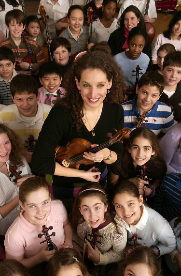Violinist and music teacher Amelia Gold poses with a violin at the Elisabeth Morrow School in Englewood, New Jersey.