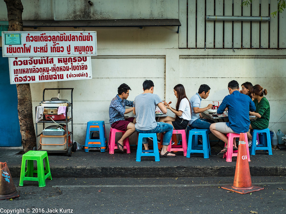 17 JANUARY 2016 - BANGKOK, THAILAND: People sit on the sidewalk at a noodle soup stand on Sukhumvit Soi 38, one of the most famous street food areas in Bangkok. The food carts and small restaurants along the street have been popular with tourists and Thais alike for more than 40 years. The family that owns the land along the soi recently decided to sell to a condominium developer and not renew the restaurant owners' leases. More than 40 restaurants and food carts will have to close. Most of the restaurants on the street closed during the summer of 2015. The remaining restaurants are supposed to close by the end of this week.           PHOTO BY JACK KURTZ