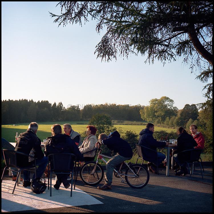 Le 22 octobre 2011, frontière Allemagne / Belgique, près d'Aix La Chapelle, RN 68. Des personnes discutent à la terrasse de l'ancien poste frontière allemand de Köpfchen transformé en bar et salle culturelle.