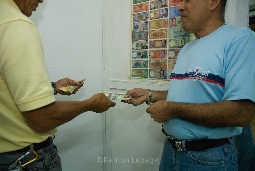 Dos venezolanos cambian dolares de mercado negro en el centro de Caracas. Muchas personas compran bienes debido al gran flujo de gastos de gobierno, créditos bancarios privados y el miedo a la inflación.  Uno de los hechos económicos más importantes, en estos años, ha sido el control monetario impuesto por la administración de Chávez, colocando el precio del dólar a 2150 bolívares mientras que en el mercado negro se vende de 3500 a 4200 bolívares, y limitando el cupo de consumo en gastos electrónicos y de viajes. Caracas, 6-03-07 (Ramón Lepage/Orinoquiaphoto)  Two Venezuelan men during black market currency exchange in downtown Caracas, March 06, 2007. Many people are buying goods due to the large cash flow from government spending, enticing private bank loans and also fears of inflation in the economy. The Chavez adminitration implemented more than 3 years ago a currency control, setting the the price of 2150 bolivares per dollar while the black market price is about 3500 to 4200 bolivares. Venezuelans are allowed to spend during the year up to  $ 5000 for travel and $3000 for internet shopping. (Ramón Lepage/Orinoquiaphoto)