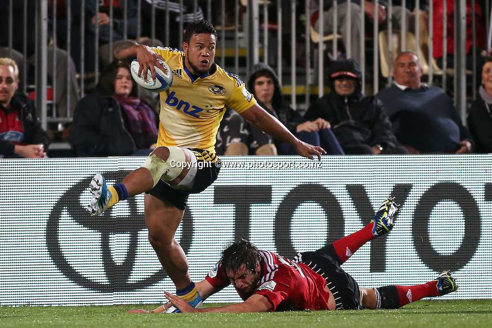 Alapati Leiua of the Hurricanes runs past the tackle of Sam Whitelock during the Investec Super Rugby between Crusaders v Hurricanes at AMI Stadium, Christchurch. 28 March 2014 Photo: Joseph Johnson/www.photosport.co.nz