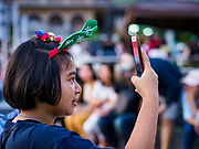 """23 DECEMBER 2018 - CHANTABURI, THAILAND: A girl wearing Christmas decorations takes a picture with her smart phone at the Cathedral of the Immaculate Conception's Christmas Fair in Chantaburi. Cathedral of the Immaculate Conception is holding its annual Christmas festival, this year called """"Sweet Christmas @ Chantaburi 2018"""". The Cathedral is the largest Catholic church in Thailand and was founded more than 300 years ago by Vietnamese Catholics who settled in Thailand, then Siam.  PHOTO BY JACK KURTZ"""