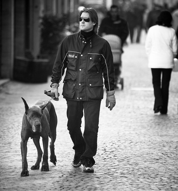 A man walks a dog, a Great Dane, along a cobbled street in Senigalia, Italy.