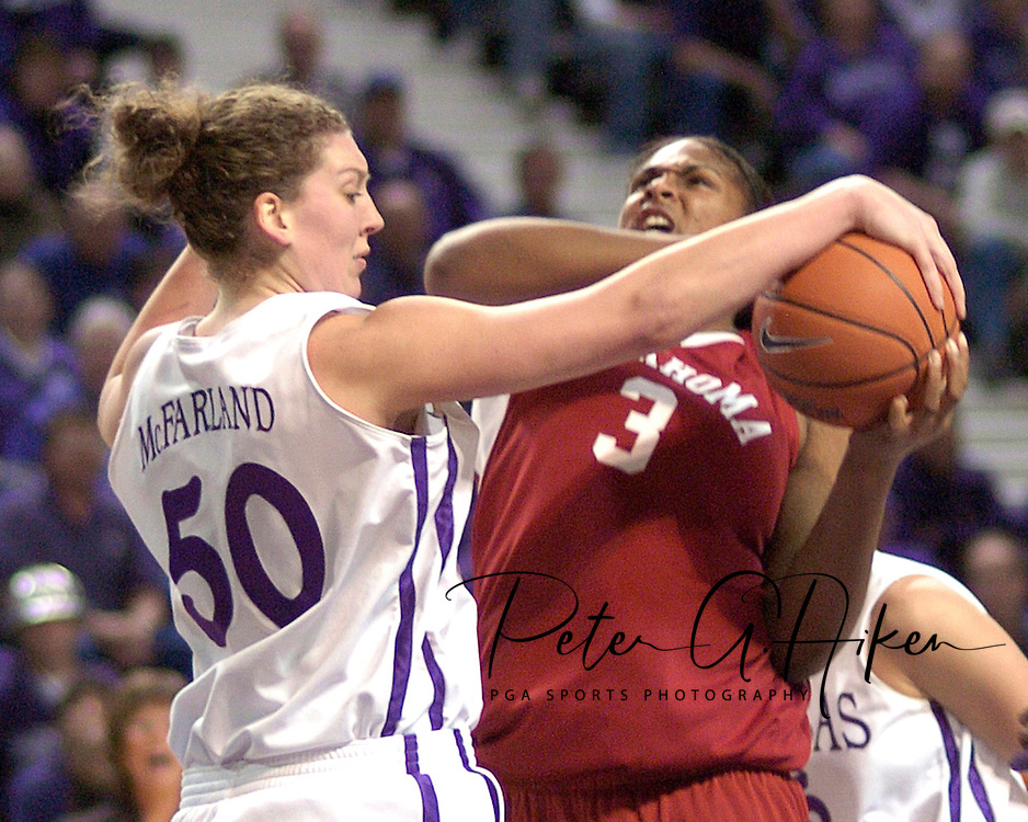 Kansas State center Jessica McFarland (L) blocks Oklahoma center Courtney Paris's (R) shot, during the first half at Bramlage Coliseum in Manhattan, Kansas, February 21, 2006.  The 9th ranked Sooners defeated K-State 78-64.