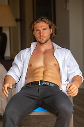 hot man in an open shirt sitting in a chair at home