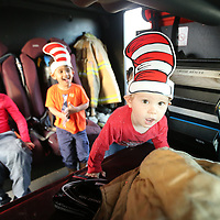Luke Rucker, 2, of Sherman, climbs over to the driverseat of Tupelo Fire Engine 6 as he gets to tour the inside after being read Dr. Seuss stories by Tupelo Fire Departmant Captain Mark Patton Thursday afternoon at McDonald's on West Main Street in Tupelo as part of Dr. Seuss week.
