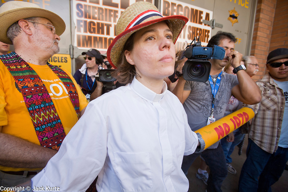 """29 JULY 2010 - PHOENIX, AZ: Rev. Susan Frederick-Gray, from the Unitarian Universalist Church in Phoenix, waits to be arrested during a blockade of the 4th Ave Jail in Phoenix Thursday.  Dozens of people were arrested during protests against SB 1070 across central Phoenix Thursday. US Judge Susan Bolton's ruling Wednesday stopped four of SB 1070's more than a dozen provisions from going into effect. She wrote, """"The court also finds that the United States is likely to suffer irreparable harm if the court does not preliminarily enjoin enforcement of these sections,"""" she states in the ruling. """"The balance of equities tips in the United States' favor considering the public interest.""""  PHOTO BY JACK KURTZ"""