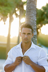 hot man buttoning a white shirt at sunset on a beach