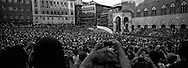 The horse turnin at the San Martino curve, the most dangerous of the race, the piazza del Campo is packed of people