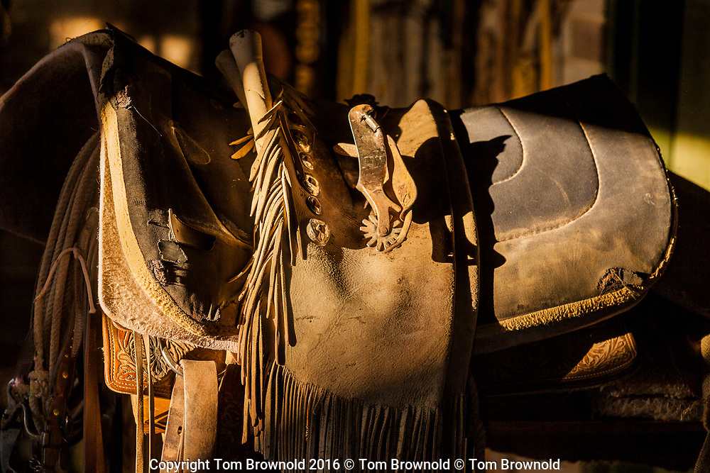 Saddle blanket with spurs,chaps and saddle in the tack room first light