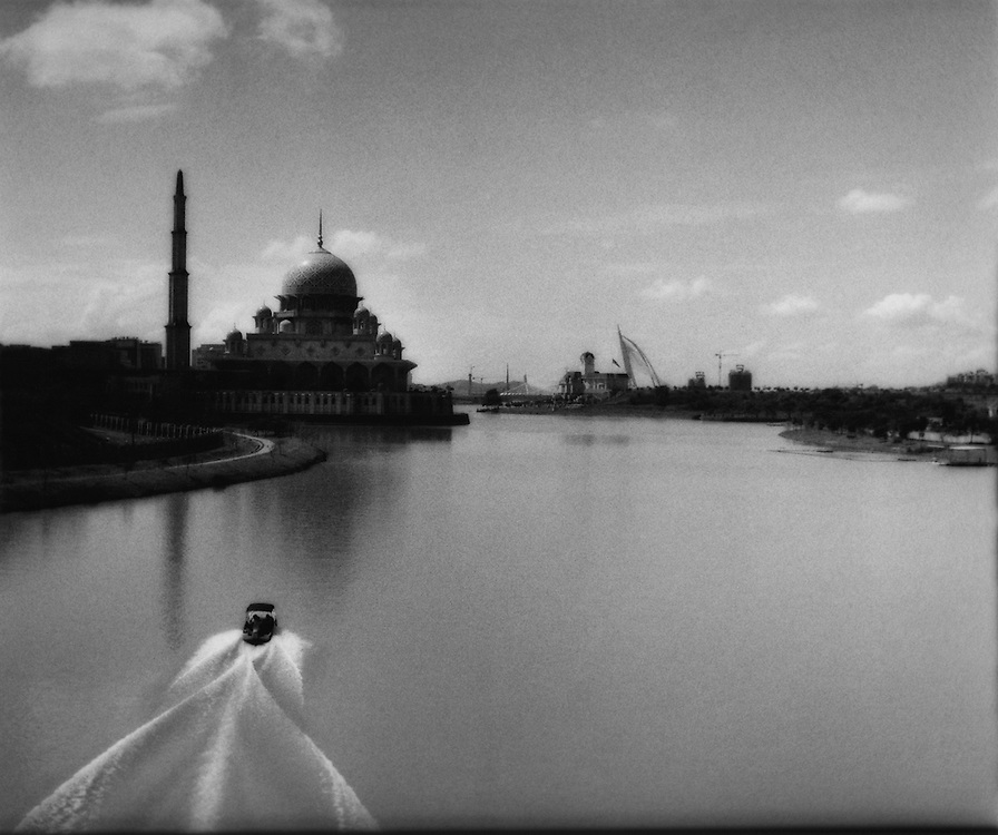 Police boat patrols passed brand new Persian-style Putra Mosque towers over artificial lakefront, Putrajaya, Malaysia.