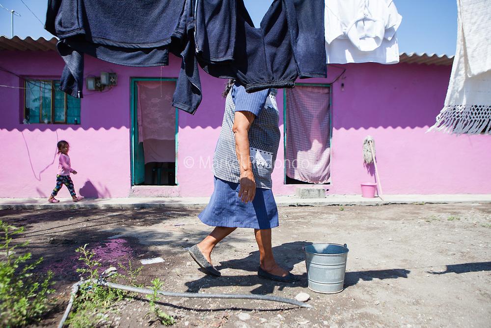 Josefina Garcia Santos accroche le linge pour le faire s&eacute;cher dans sa maison d'Aztla, Puebla. Son mari et sa fille sont aux Etats-Unis depuis 6 ans. Elle est seule &agrave; &eacute;lever sa petite-fille en l'absence de sa m&egrave;re qu'elle n'a pas vu depuis 6 ans.<br /> <br /> Josefina Garcia santos con su nieta en las calles de Aztla, Puebla. Josefina tiene su marido y su hija en USA desde hace 6 anos. Ella cuida y crea a su nieta en ausencia de su madre que hace seis anos que no la ve.