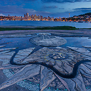 A decorative concrete inlay in Gasworks Park over looking the Seattle city skyline just as the  sun sets in Washington.