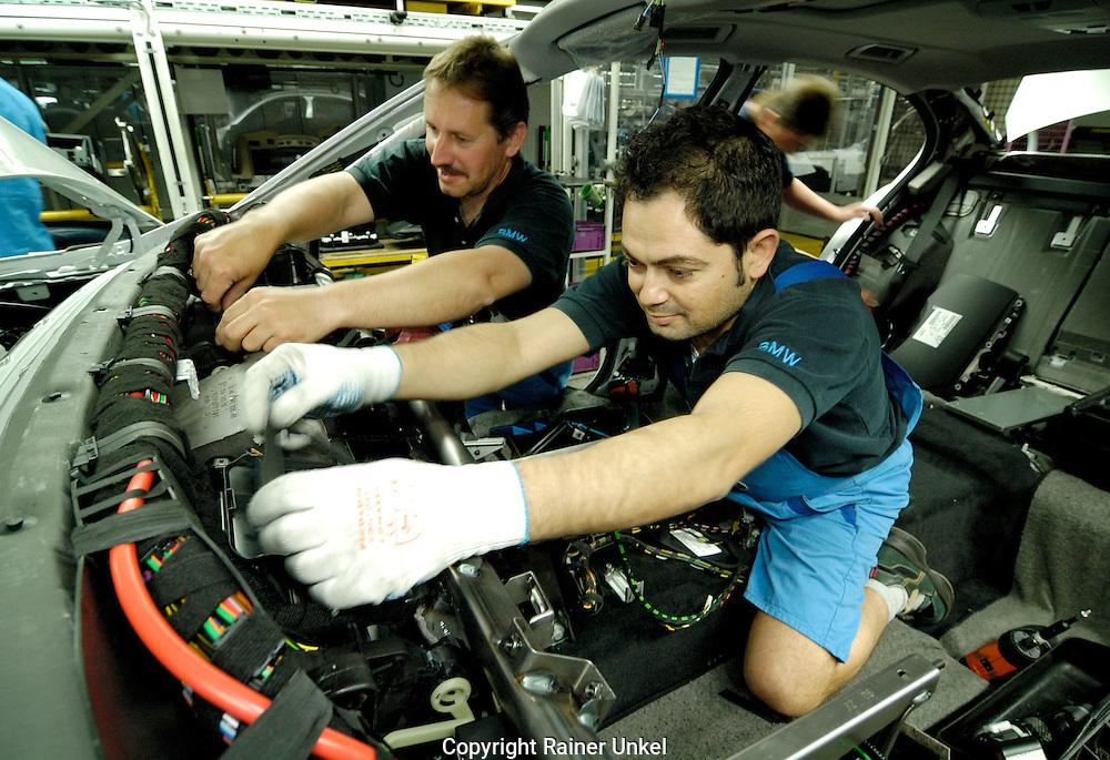 DEUTSCHLAND : Autoproduktion bei BMW in Dingolfing : Arbeiter beim Innenausbau.   GERMANY : Car production at BMW in Dingolfing : work on the car interior.   16.04.2007.   Foto: Copyright by Rainer UNKEL, Tel.: (0)228/477211, Fax: (0)228/477212.