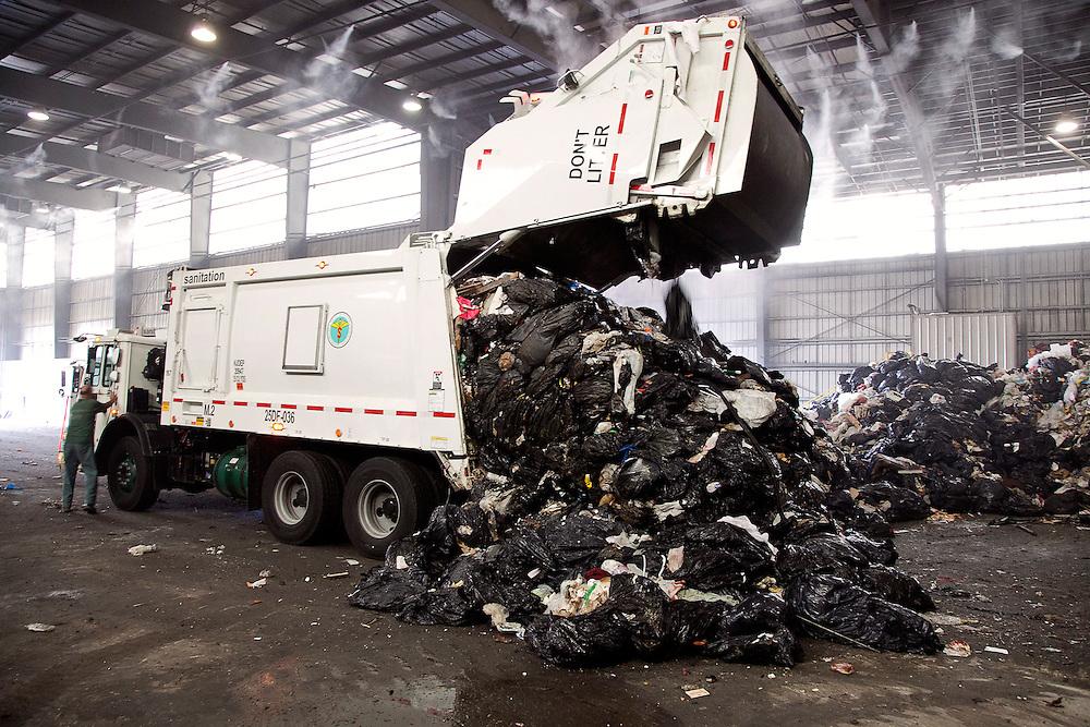 back loader waste collection truck dumps solid waste on tipping floor of transfer station