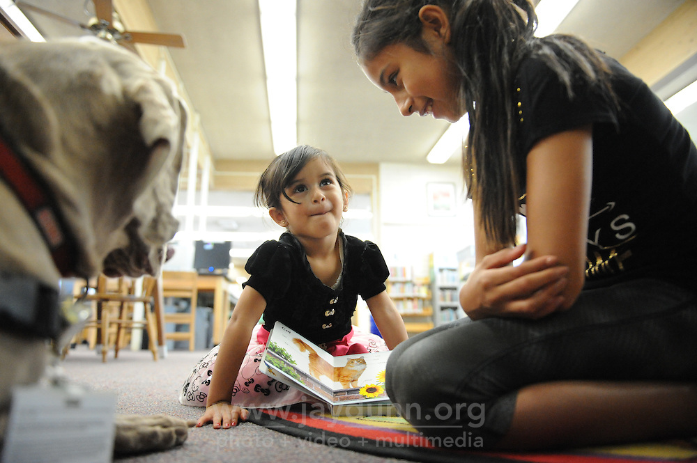 With her sister Isabella, 10, Penelope Virgen, 3, reads from a book of pets to Stormy Blue Bailey, a Weimaraner dog at the Steinbeck Public Library in Salinas.